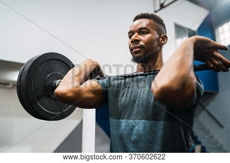 Portrait Of Young Athlete Doing Exercise With A Barbell. Sport And Healthy Lifestyle Concept.