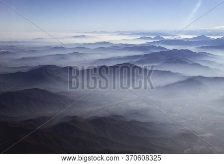Clouds Linger Over Hills Stretching Into Distance, As Photographed From Airplane Window Flying Over