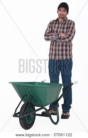 Tradesman standing behind a wheelbarrow