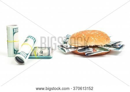 Burger With Hundred Dollar Bills Instead Of Toppings And Rolls Of Hundred Dollar Bills On A White Ba