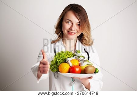 A Young Nutritionist Holding In Her Hands Fresh Vegetables And Fruits On Plate In The Consultation R