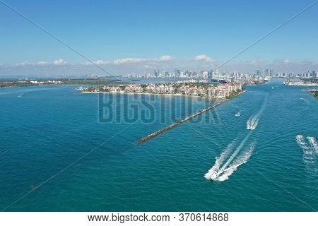 Aerial View Of Fisher Island, South Pointe And Government Cut With City Of Miami Skyline And Port Mi