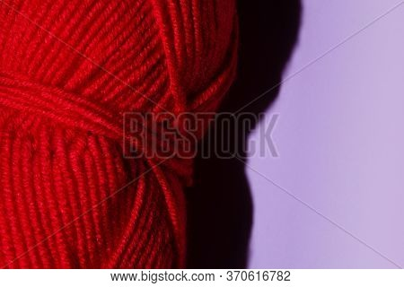 Red Skein Of Thread For Knitting On A Purple Background, Copy Space. Macro