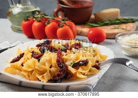 Pasta With Sun-dried Tomatoes And Parmesan In A White Plate On The Table. Italian Cuisine, Ingredien