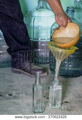Mezcal Is Poured Into A Bottle For Sale From A Small Distillery.