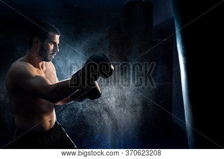 Thai Boxing Fighter On A Dark Background Hits A Boxing Bag. Advertising Martial Arts Fitness Center