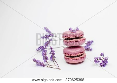 Appetizing Pink (purple) Macaroons Cookies And Flowers On A White Background. Lavender Cookies