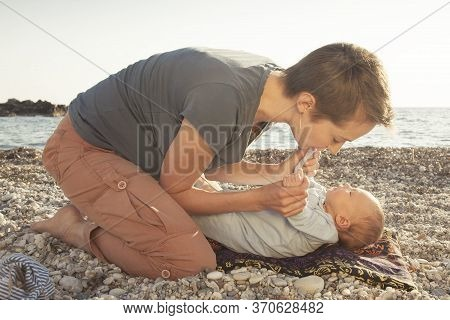 Mom Kisses And Hugs Her Newborn Baby. Parent Shows Feelings For His Baby. Mother And Child Spend Tim