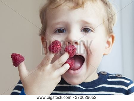 Adorable Little Boy Eating Fresh Ripe Raspberries. Healthy Food And Snack For Kids Concept.