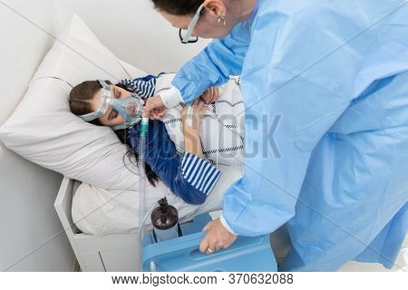 The Doctor Controls The Connection Of The Ventilator. The Teenager Lies On A Hospital Bed. Oxygen Ma