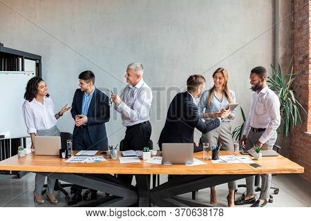 Corporate Lifestyle And Communication. Multiracial Coworkers Communicating Standing Near Table Durin