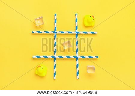 Duck Toy, Ice Cubes, Paper Tubes With Blue Stripes For Drinks On A Yellow Background. Sea Battle, Ti