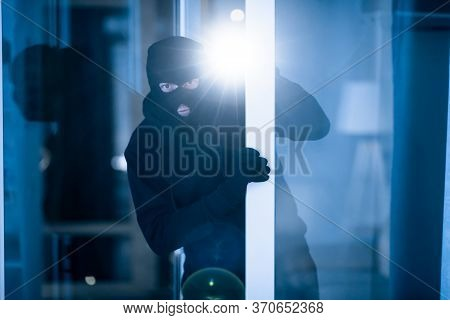 Burglary Concept. Evil Intruder Wearing Black Mask Peeking Into House Through Window Or Glass Door,