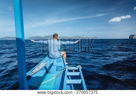 Back View Of The Man With Raised Hands On The Boat And Looking At Open Sea. Travelling Tour In Asia: