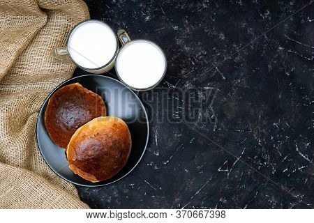 Two Homemade Buns On A Black Plate, Two Glasses Of Milk And A Burlap Cloth On A Black Texture Backgr