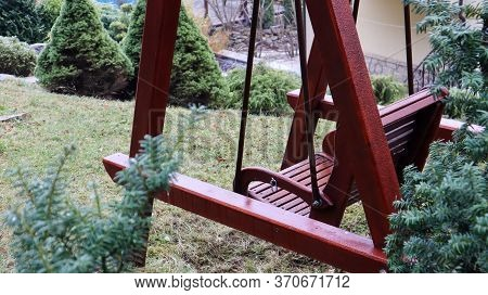 A Backyard Swing Is Ideal For Relaxing. Garden Old Wooden Swing In The Backyard Of A Rural House