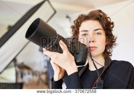 Young woman as a photo student or photographer with digital camera