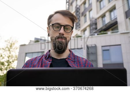 Concentrated Bearded Man Looking At Laptop. Dark-haired Freelancer Sitting In Park With City Buildin