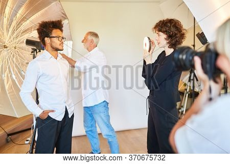Man as a model posing in front of studio light for portrait photos in the photo studio