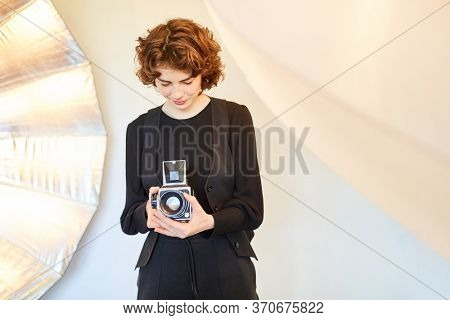 Young photographer inspects camera settings of her medium format camera