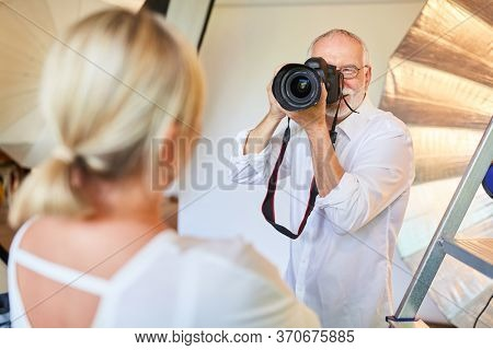 Photographer with digital camera takes portrait photos of woman in the photo studio