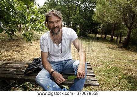 Handsome Mature Man Sitting On A Wooden Bench And Laughing In A Natural Parkland. Bearded And Happy