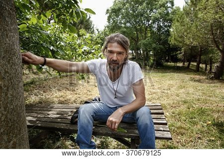 Handsome Mature Man Sitting On A Wooden Bench And Touching A Tree In A Natural Parkland. Bearded Man