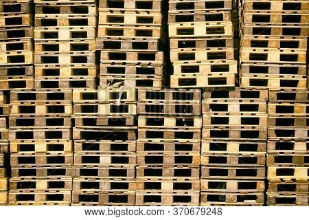 Pallets Background. Stacks Of Brown Rough Wooden Pallets At Warehouse In Industrial Yard. Cargo And