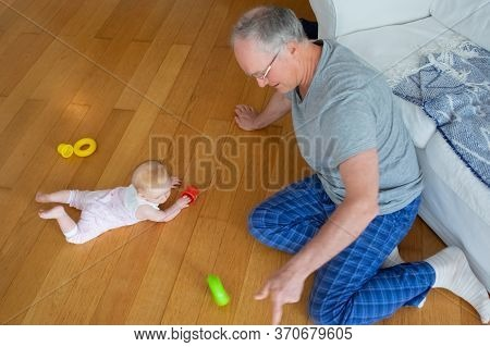 Grey Haired Grandpa In Home Clothes Playing With Baby Granddaughter On Living Room Floor. Child Craw