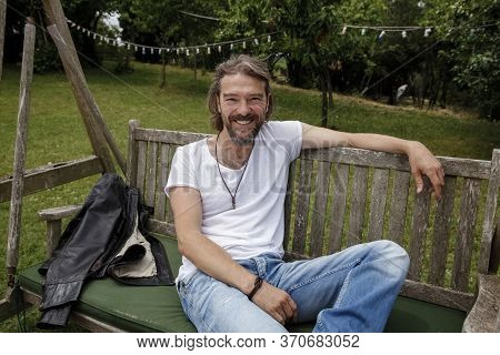 Portrait Of A Handsome Man Sitting On A Wooden Garden Swing Seat In A Natural Parkland And Laughing.