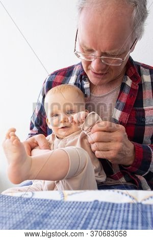 Cheerful Happy Baby Girl Sitting On Grandpa Knees At Dining Table. Front View, Vertical Shot. Family
