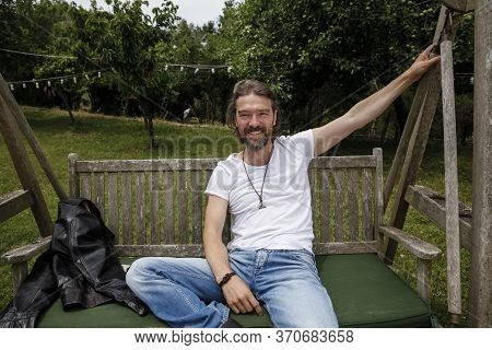 Portrait Of A Handsome Man Sitting On A Wooden Garden Swing Seat In A Natural Parkland And Smiling.