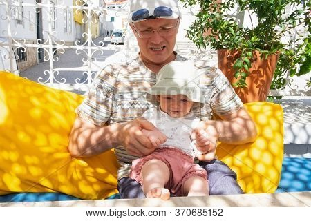 Happy Sweet Baby Girl Sitting On Grandpa Knees On Outdoor Terrace In Summer. Front View. Family Or B