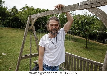 Handsome Mature Man Sitting On A Wooden Bench And Smiling In A Natural Parkland. Bearded And Happy M