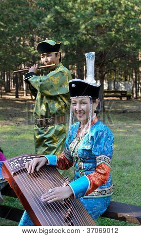 ULAN-UDE, RUSSIA - SEPTEMBER 13: Unidentified man and woman playing on the Buryat instruments. Costume show for the guests of  Baikal Economic Forum., September 13, 2012 in Ulan-Ude, Buryatia, Russia