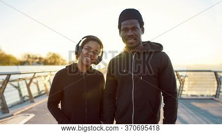 Morning Jog. Young Happy African Couple Runners In Headphones Standing On The Bridge Outdoors And Sm