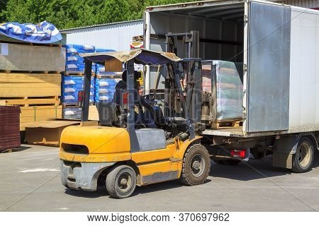 Yellow Forklift Loader Loads Cargo Into Truck For Delivery To Customers