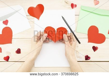 Womans Hands Are Holding A Torn Paper Red Heart. Loss Of Love, Message, Letter.