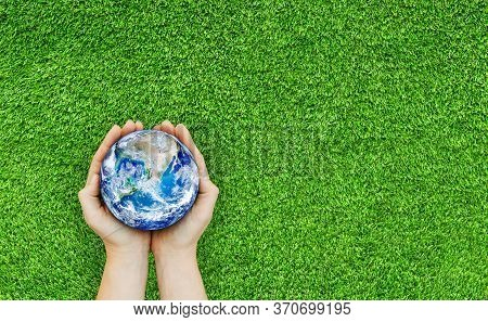 Ecology And Environment Concept : Top View Of Hand Holding Blue Planet Earth Over Green Grass. (elem