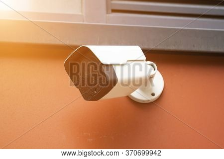Dirty Closed-circuit Television Camera Mounted On Orange Outdoor Wall. Cctv Security Camera Outdoors