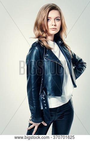Charming young woman with blonde hair and beautiful blue eyes posing in black leather jacket and leather pants on a white background. Beauty, fashion.