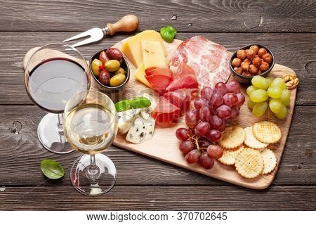 Cheese, meat, grapes and olives antipasto. Appetizer selection on wooden board and glasses with red and white wine
