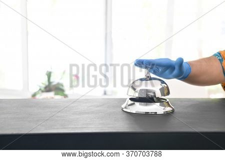 Coronavirus free tourism concept; customers ring hotel bell using gloves at new normal