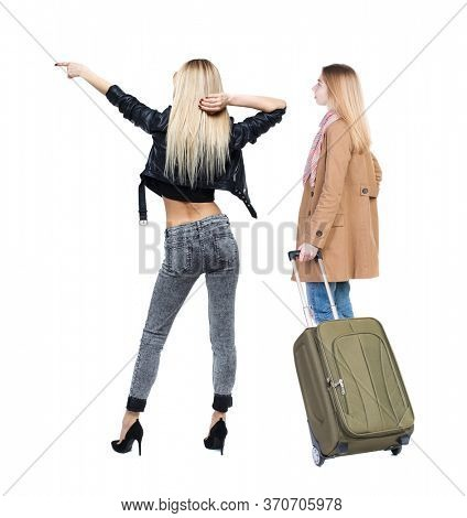Back view of two woman in winter jacket traveling with suitcas. Back view. Rear view people collection. backside view of person. Isolated over white background.