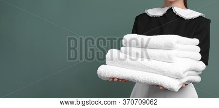 Young Chambermaid Holding Stack Of Clean Towels On Color Background, Closeup View With Space For Tex