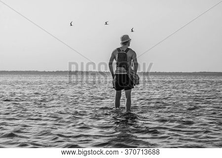 Lonly Man On Sea Water With Birds In Bw