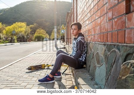 A Teenage Boy Sits On The Sidewalk Next To A Scooter And Looks Sadly Into The Distance. Brick Wall A