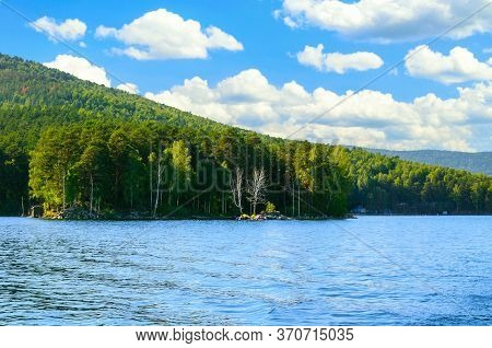 Summer mountain water landscape - Turgoyak Lake in Southern Urals, Russia. Summer sunny water landscape, summer mountain scene with water, mountain lake view, summer water mountain background.