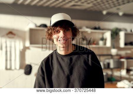 Stylish Guy Smiling At Camera While Posing In Custom Apparel, Black Baseball Cap And Sweatshirt. You