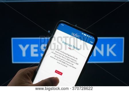 A Mobile Logged Into The Yes Bank Mobile Application Infront Of The Yes Bank Board